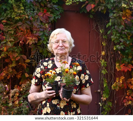 pensioner beautiful woman with pot plants on the country autumn background