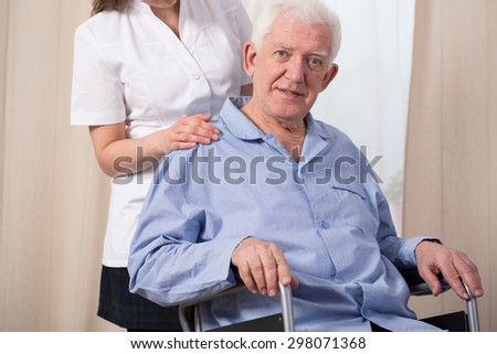 Pensioner dressed in pyjama and sitting in a wheelchair - stock photo