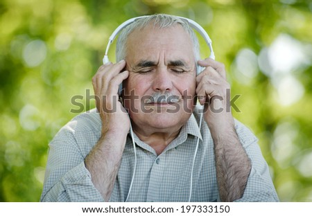 Pensioner enjoying his music sitting with his eyes closed in pleasure as he listens to a tune on his headphones while sitting out in the garden - stock photo