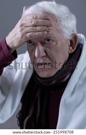 Pensioner having high fever touching his forehead - stock photo