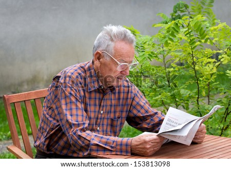 Pensioner reading newspapers in backyard - stock photo