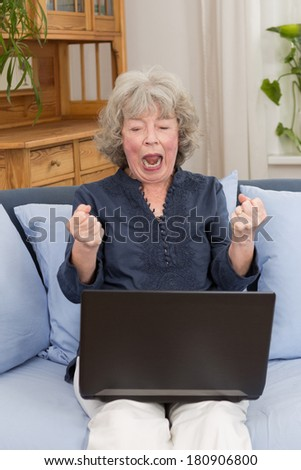 Pensioner sitting on a sofa screaming at her laptop with clenched fists
