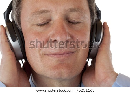 Pensioner with headphones listening to mp3 music. Isolated on white background. - stock photo