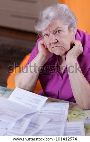 Pensioner with papers before her, looking desperately to the viewer - stock photo
