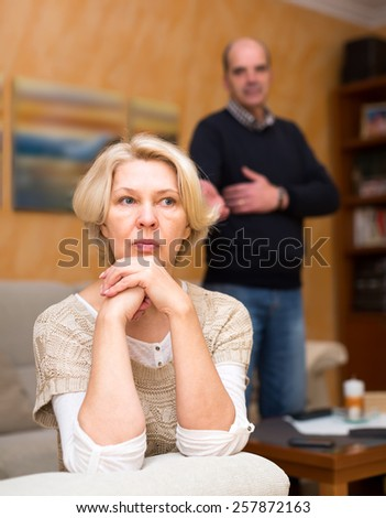 Pensioners couple are having a quarrel. Mature wife is sitting turned away from her old husband with her arms near her cheek and the husband is standing behind and talking to her