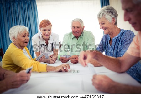 Pensioners playing cards with nurse in the retirement house