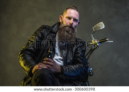 Pensive Adult Bearded Man with a Bottle of Drink Sitting on his Motorcycle and Looking Into the Distance Against Smoky Background. - stock photo