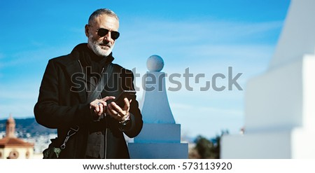 Pensive adult man wearing black aviator sunglasses and using smartphone while spending time in city park.Horizontal wide,blurred background