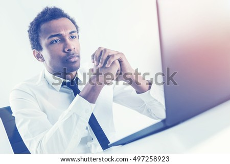 Pensive african american businessman with tie sitting at office desktop using laptop. Toned image