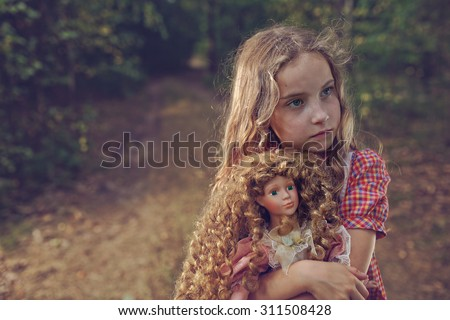 Pensive and mysterious young girl with a doll - stock photo