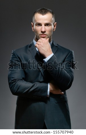 Pensive and self-confident man props head with hand - stock photo