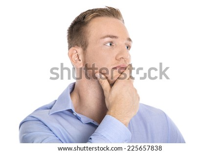 Pensive and unhappy isolated young blond businessman in blue shirt looking sideways to text. - stock photo