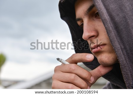 pensive and worried teenage boy with black hoodie is smoking cigarette outdoor. Harmful smoking concept - stock photo