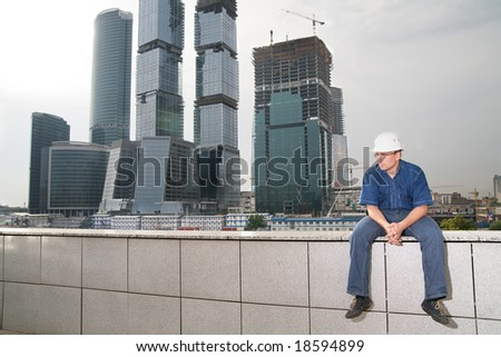 Pensive architect wearing a protective helmet sitting in front of a building site