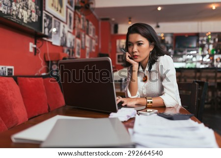 Pensive Asian bar owner using laptop to pay bills online - stock photo
