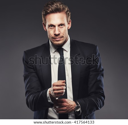 Pensive attractive businessman adjusting his cuff on his shirt as he stands looking at the camera with a quiet smile, upper body on grey