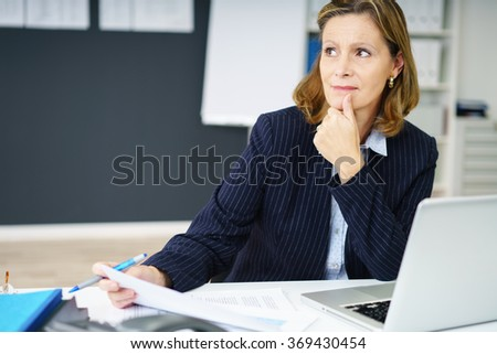 Pensive attractive middle-aged businesswoman watching something to the left of the frame as she holds a document in her hand - stock photo