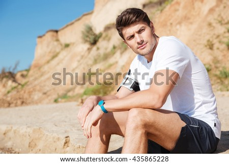Pensive attractive young man sitting on the beach
