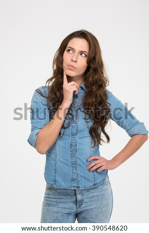 Pensive attractive young woman standing and thinking over white background - stock photo