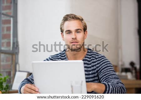 Pensive attractive young young man sitting at his laptop staring at the camera with a serious contemplative expression - stock photo