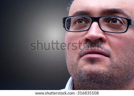 Pensive bearded caucasian man wearing eyeglases isolated on a dark background - stock photo