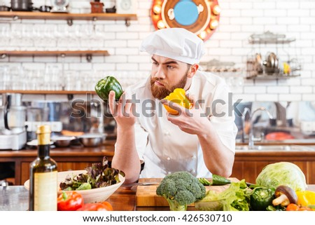 Pensive bearded chef cook choosing fresh vegetables for salad on the kitchen - stock photo