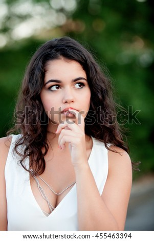 Pensive beautiful brunette girl relaxing in the park wiht many plants of background - stock photo