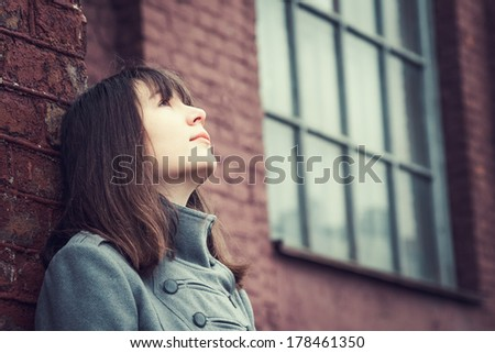 pensive beautiful young girl standing near a brick wall and looking up - stock photo