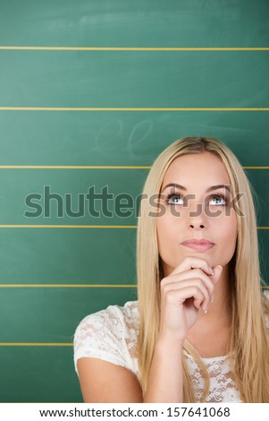 Pensive beautiful young student with long straight blond hair standing in front of a blank green blackboard with her eyes raised and her hand to her chin - stock photo