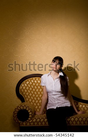 pensive beautiful young woman brunette woman sitting on sofa in room - stock photo