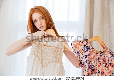 Pensive beautiful young woman desiding what to wear and choosing dress at home