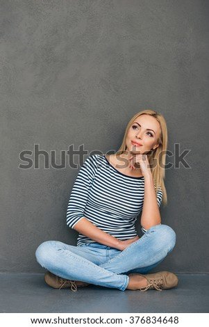 Pensive beauty. Beautiful young woman holding hand on chin and looking away with smile while sitting in lotus position against grey background - stock photo
