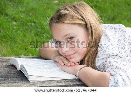 Pensive Blond girl at park with book looking at the camera