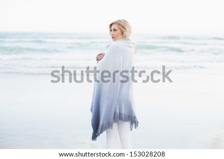 Pensive blonde woman warming herself in a blanket on the beach