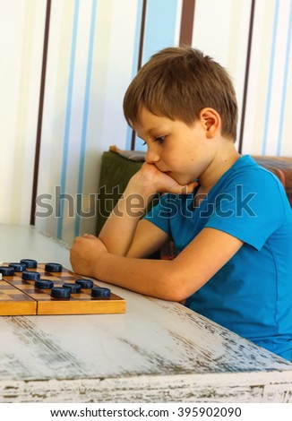 Pensive boy during a game of checkers - stock photo
