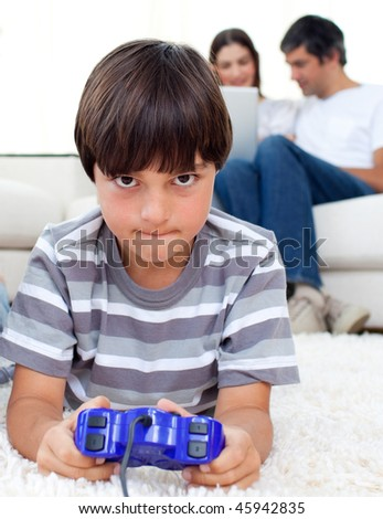 Pensive boy playing video games lying on a floor - stock photo