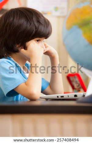 pensive boy sitting at a table with a laptop - stock photo