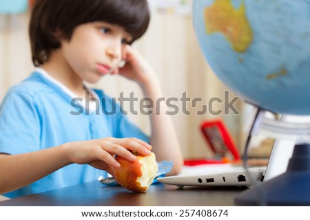 pensive boy sitting at a table with a laptop and eating apple. focus on fruit - stock photo