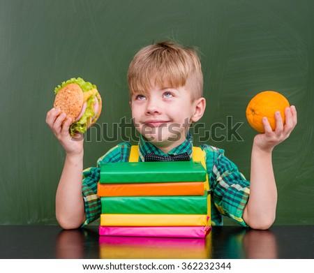 Pensive boy with orange and hamburger - stock photo