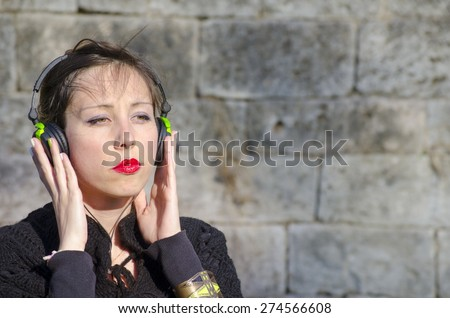 Pensive brunette listening to music on a headset outdoors - stock photo