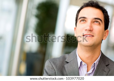 Pensive business man looking up and smiling - stock photo
