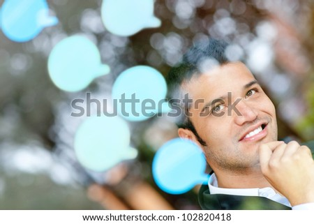 Pensive business man with thought bubbles around his head - stock photo