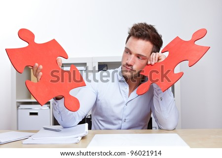 Pensive business man with two oversized red jigsaw puzzle pieces in office - stock photo