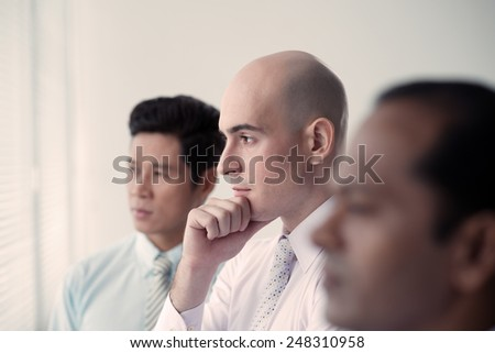 Pensive business people looking through the window, side view - stock photo