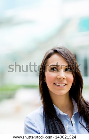 Pensive business woman looking up and smiling - stock photo