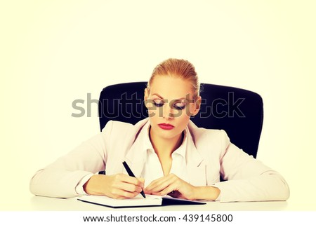 Pensive business woman taking notes behind the desk - stock photo