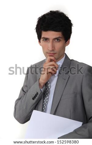 Pensive businessman holding paperwork - stock photo