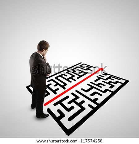 pensive businessman in front of labyrinth - stock photo