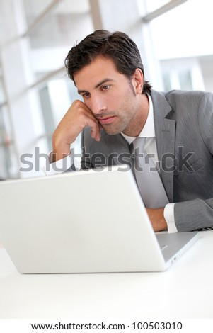 Pensive businessman in front of laptop