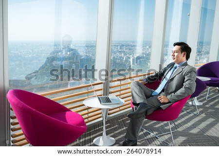 Pensive businessman looking at the city through the office window - stock photo